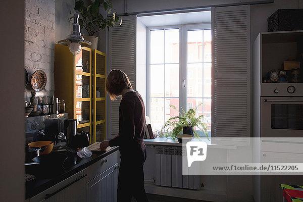 Frau am Küchentisch beim Zubereiten von Essen