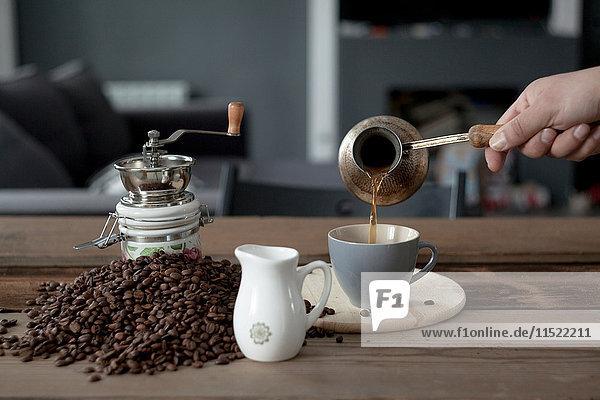 Ausschnitt eines Mannes  der Kaffee aus der Kaffeekanne gießt
