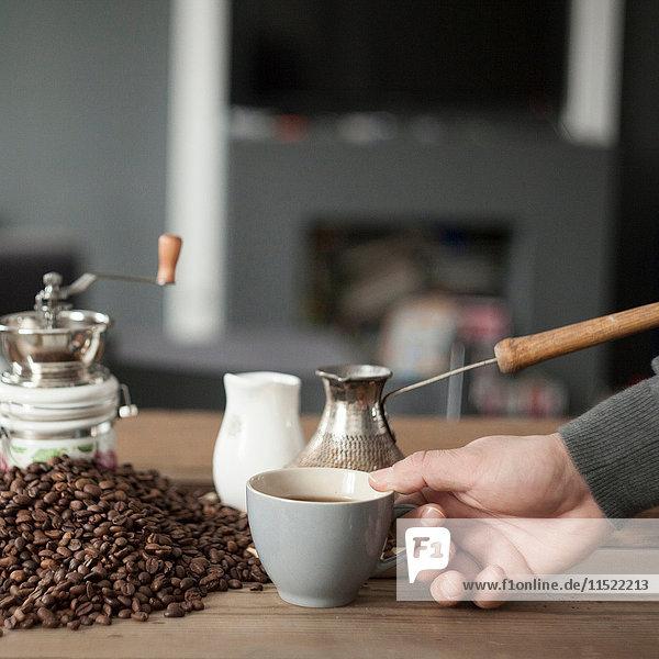 Ausschnitt eines Mannes  der eine Kaffeetasse aufhebt