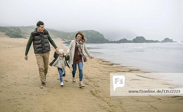 Glückliche Familie mit Tochter  die im Winter am Strand spazieren geht.