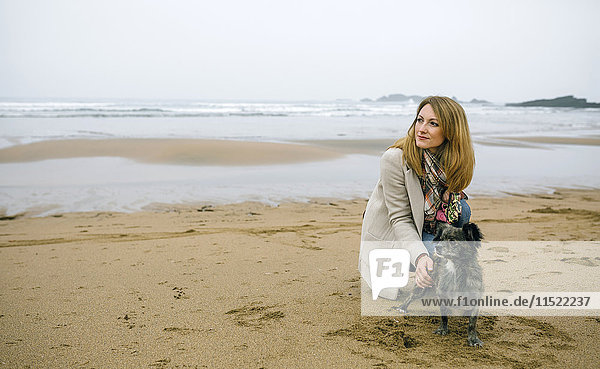 Woman stroking dog on the beach in winter