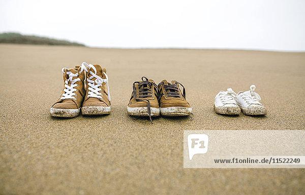 Drei Paar Schuhe mit verschiedenen Größen am Strand
