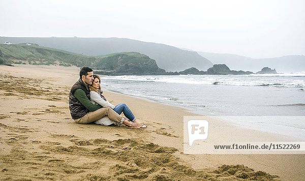 Couple in love sitting on the beach in winter