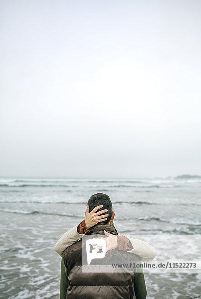 Frau umarmt Mann an der Strandpromenade im Winter