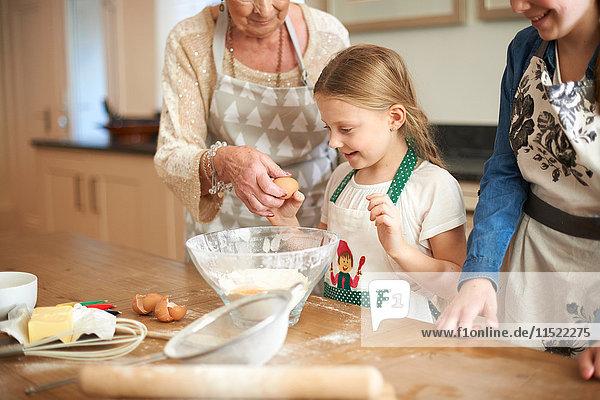 Ältere Frau und Enkelinnen knacken Eier für Kekse