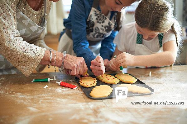 Schnappschuss einer älteren Frau und Enkelinnen beim Dekorieren von Weihnachtsbaumplätzchen