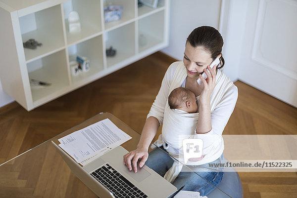 Mutter mit Mädchen im Tragetuch bei der Arbeit von zu Hause aus