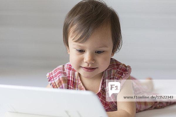 Porträt des Inhalts kleines Mädchen beim Betrachten des digitalen Tabletts