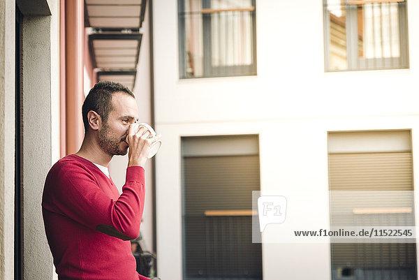 Mann auf dem Balkon trinkt Kaffee Mann auf dem Balkon trinkt Kaffee