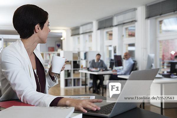 Frau mit Laptop im Büro im Gespräch mit Kollegen im Hintergrund