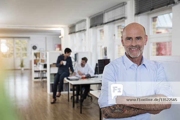 Porträt eines selbstbewussten Mannes im Amt mit Kollegen im Hintergrund
