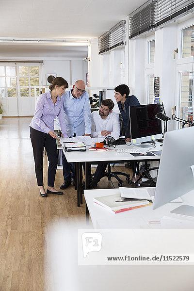 Kollegen  die gemeinsam am Schreibtisch im Büro arbeiten
