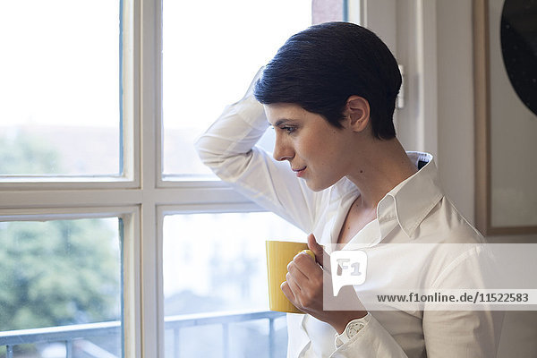 Woman holding cup of coffee looking out of window