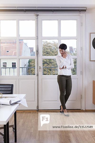 Frau steht am Fenster im Büro und redet am Telefon