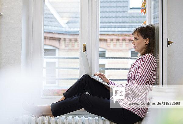 Frau mit Laptop am Fenster