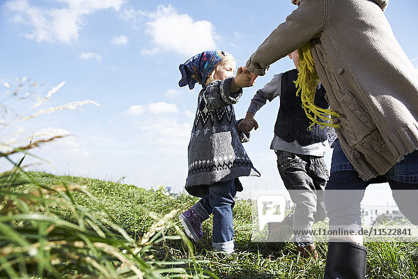 Three children playing ring-a-ring-a-roses in meadow