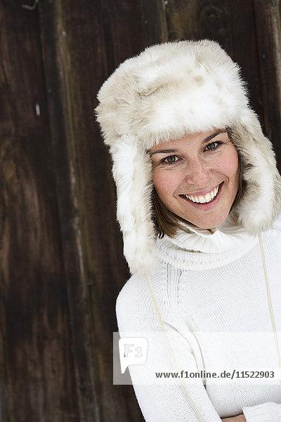 Portrait of smiling woman wearing fur cap in winter