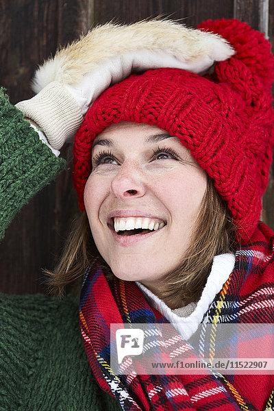 Porträt einer lächelnden Frau mit rotem Bommelhut und Pelzhandschuhen im Winter