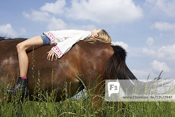 Girl lying on horseback