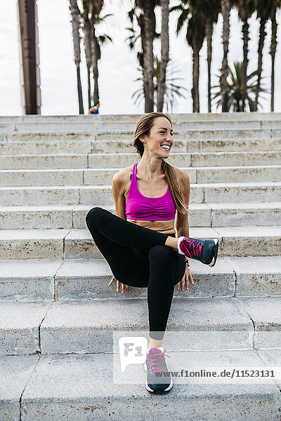 Junge Frau nach dem Training auf der Treppe sitzend