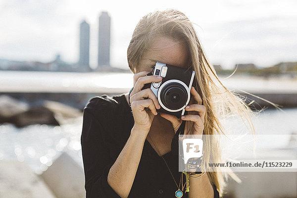 Junge Frau fotografiert mit altmodischer Kamera an der Strandpromenade