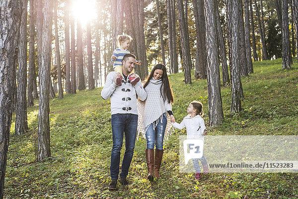 Glückliche Familie mit zwei Mädchen  die im Wald spazieren gehen.