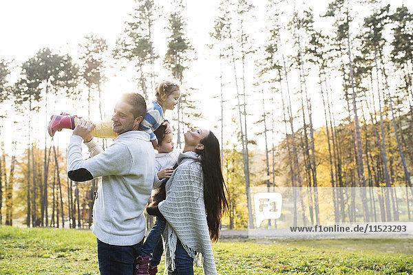 Verspielte Familie mit zwei Mädchen im Freien