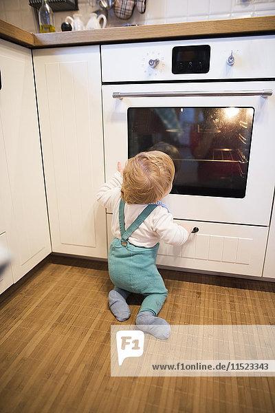 Junge sitzt in der Küche und schaut Kuchen backen im Ofen.