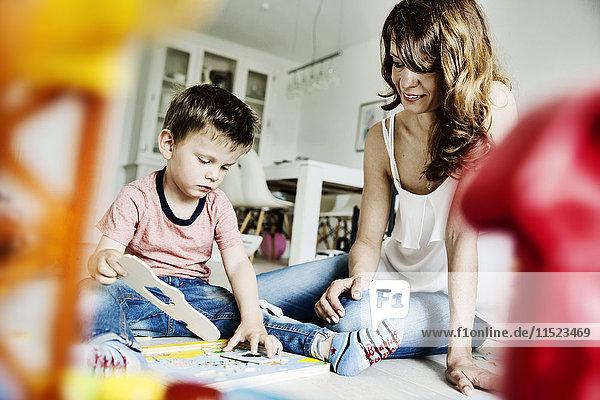 Mutter und Sohn  die im Wohnzimmer arbeiten