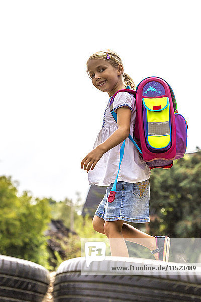 Smiling little girl with school bag on playground