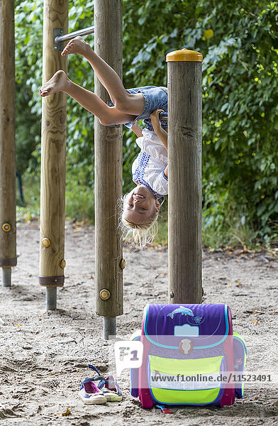 Smiling little girl with school bag on high bar of a playground