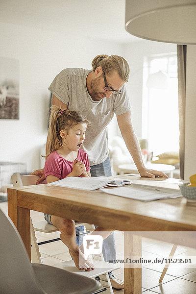 Vater prüft Hausaufgaben seiner Tochter