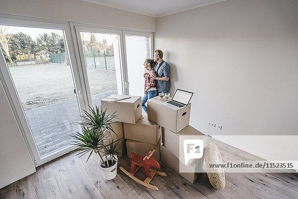 Ein glückliches Paar steht am Fenster seines neuen Zuhauses. Ein glückliches Paar steht am Fenster seines neuen Zuhauses.