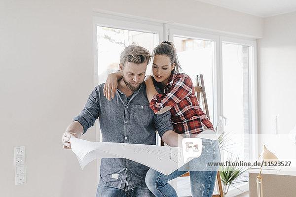 Ein Paar schaut sich den Grundriss des neuen Hauses an.