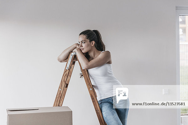 Mature woman standing in her new home  leaning on ladder