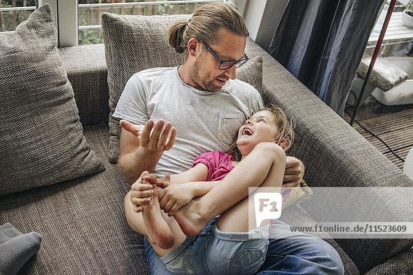 Vater spielt mit Tochter auf Sofa