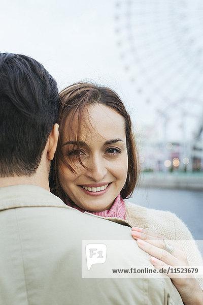 Porträt einer lächelnden Frau  die ihren Freund umarmt.