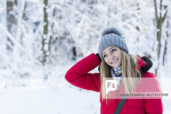 Portrait of smiling young woman in snow-covered nature