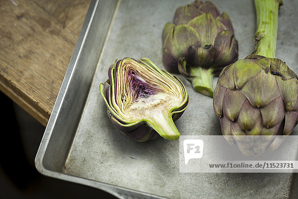Whole and sliced artichokes on baking tray
