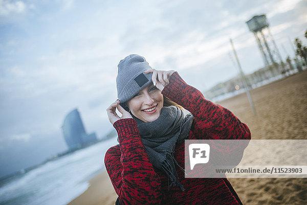 Porträt der lächelnden jungen Frau am Strand im Winter