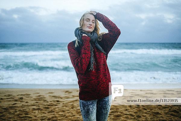 Junge Frau mit geschlossenen Augen am Strand im Winter