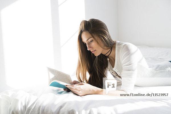 Junge Frau auf dem Bett liegend Lesebuch