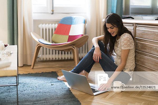 Junge Frau sitzt zu Hause auf dem Boden mit dem Laptop