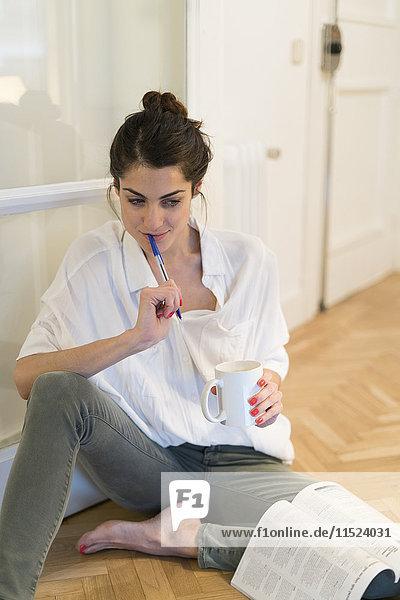 Nachdenkliche junge Frau auf dem Boden sitzend mit Kaffeetasse und Kugelschreiber