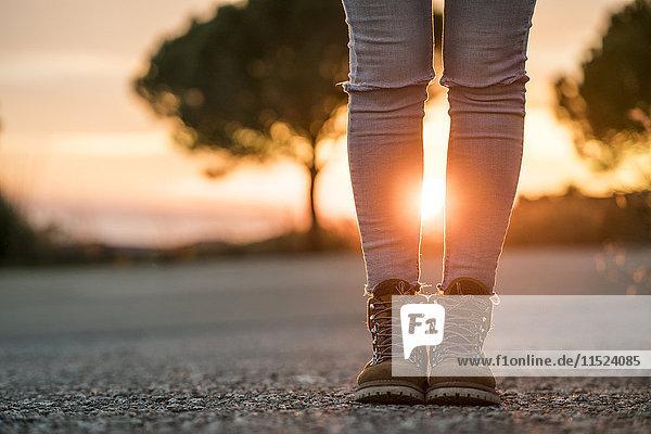 Frau in Wanderschuhen  die bei Sonnenuntergang auf der Straße steht.