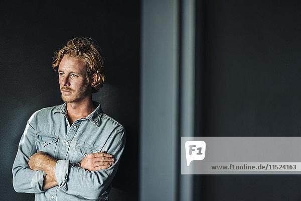 Porträt eines selbstbewussten blonden Mannes mit weißem Hemd