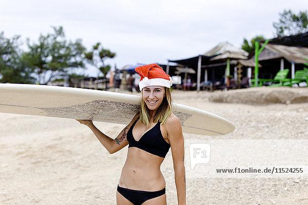 Indonesien  Bali  lächelnde Frau mit Surfbrett am Strand mit Weihnachtsmütze