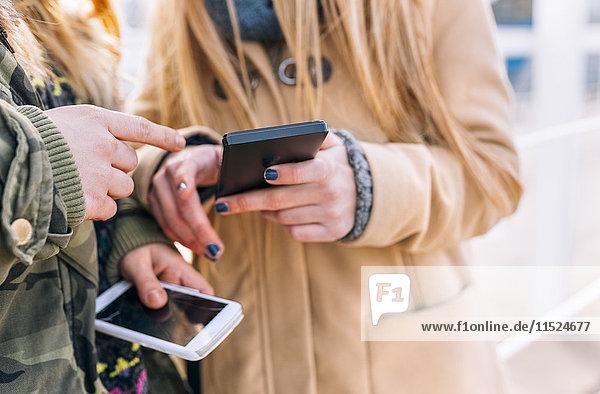 Zwei Freunde mit ihren Smartphones  Teilansicht