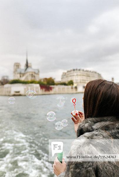 Paris  Frankreich  Touristen  die eine Kreuzfahrt auf der Seine machen und Seifenblasen blasen.