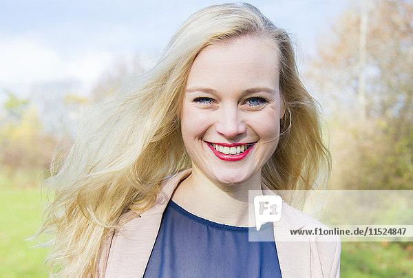 Porträt einer lächelnden jungen blonden Frau im Freien